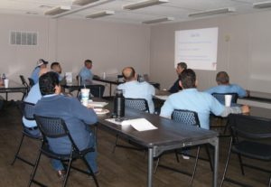 Pest control technicians grouped together in classroom attending a continuing education course.